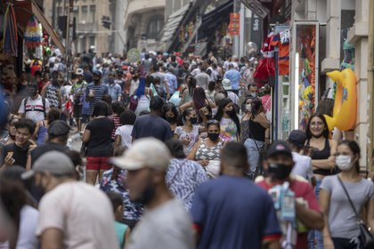 Shoppers wearing protective masks walk on 25 de Marco street in Sao Paulo, Brazil, on Friday, Dec. 18, 2020. This week Brazil reached 7 million coronavirus cases as infections pick up pace just ahead of the holiday season.