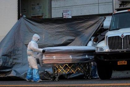 Trabajadores de una funeraria de Nueva York acarrean el atáud de una de las 200 mil víctimas mortales del coronavirus en EEUU (REUTERS/Brendan McDermid)