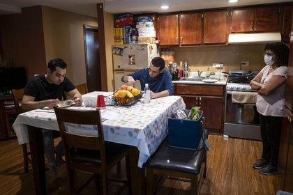 Alex González come con su hermano Sergio, mientras su madre Irene se para junto a ellos.
