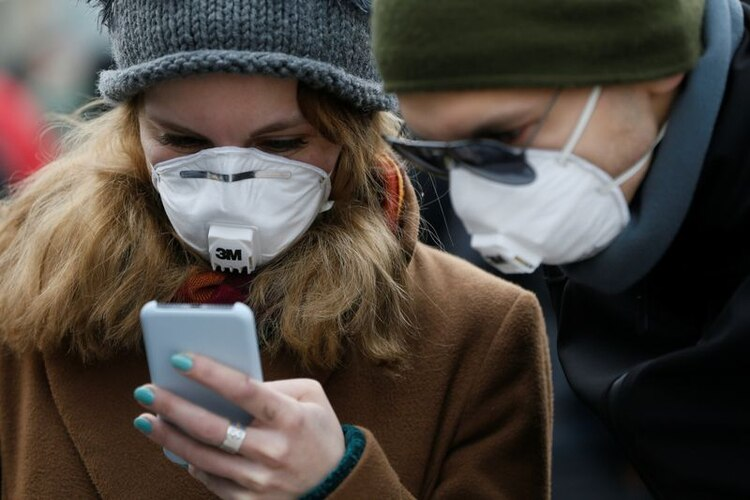 Personas utilizando mascarillas mientras usan sus teléfonos inteligentes en una calle durante el brote de COVID-19, la enfermedad que causa el coronavirus, en Kiev, Ucrania (REUTERS/Valentyn Ogirenko)