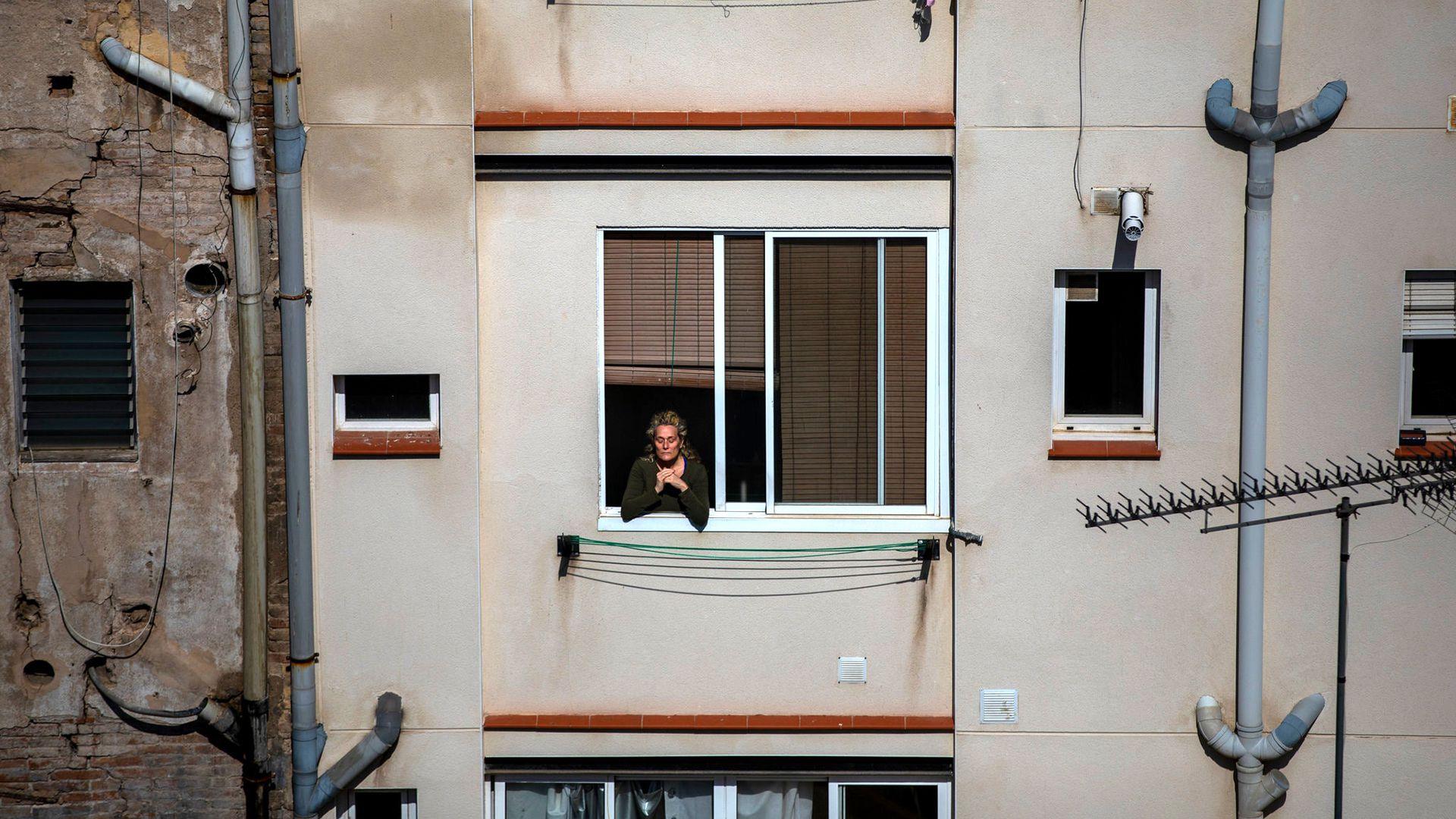 Una mujer se asoma por su ventana durante el confinamiento por el coronavirus, en Barcelona. Emilio Morenatti/Associated Press