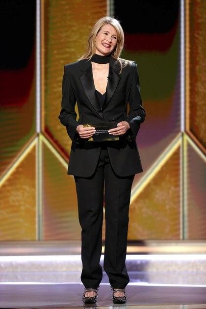Laura Dern este año eligió para los Golden Globes un esmoquin negro de mujer con camisa negra completando con accesorios de chal a tono, y zapatos cerrados del mismo color con el distintivo fashionista de tener tachas en todo el diseño. Optó por cabello suelto y maquillaje al natural resaltando sus labios