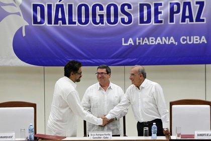 """El segundo jefe de las FARC y líder de los delegados de la guerrilla, Luciano Marín, alias """"Iván Márquez"""" saluda al jefe de la delegación de paz del Gobierno colombiano, Humberto de la Calle , en agosto de 2016 (EFE)"""