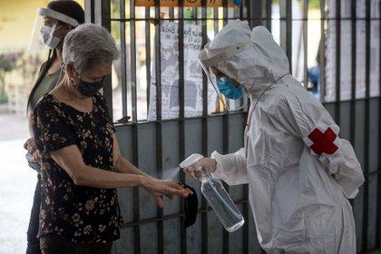 Personal sanitario rocía líquido desinfectante a una mujer