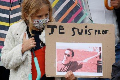 Una niña sostiene una pancarta con una foto de Samuel Paty durante un homenaje en la Place de la Republique, en Lille (Francia), el 18 de octubre de 2020 (REUTERS/Pascal Rossignol)