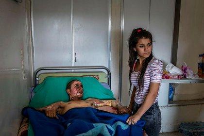 """""""Un combatiente kurdo herido recibe una visita en el hospital"""" (Ivor Prickett para el New York Times)"""