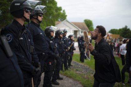 Un manifestante sostiene una pancarta mientras salta en repetidas ocasiones para que los policías que se encuentran al fondo puedan verlo el miércoles 27 de mayo de 2020 en la casa del agente Derek Chauvin, quien fue despedido de la policía de Minneapolis, a las afueras de Oakdale, Minnesota (Jeff Wheeler/Star Tribune vía AP)