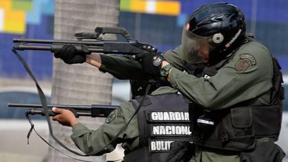 Miembros de la Guardia Nacional apuntan contra manifestantes en una de las marchas contra el régimen de Maduro