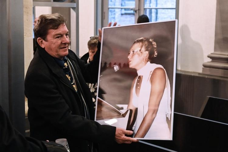 En esta foto tomada el 21 de noviembre de 2019, Jacky Kulik, el padre de Elodie Kulik, quien fue violada y asesinada en 2002, posa con un retrato de su hija en el tribunal de Amiens, antes de la apertura del juicio contra Willy Bardon (DENIS CHARLET / AFP)