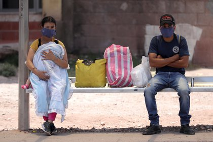 Dos personas esperan en un paradero de autobuses, en Tegucigalpa (Honduras). EFE/Gustavo Amador/Archivo