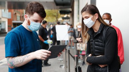 Un empleado de Apple asiste a una clienta en la calle, para agilizar su estadía en la tienda una vez que ingrese