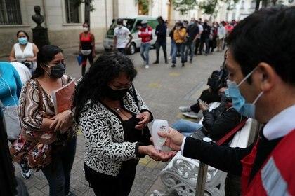 Un trabajador de seguridad le da alcohol gel a una mujer, mientras la gente hace fila frente a una sucursal de AFP (Administradoras de Fondos de Pensiones), en Santiago, Chile. REUTERS/Iván Alvarado