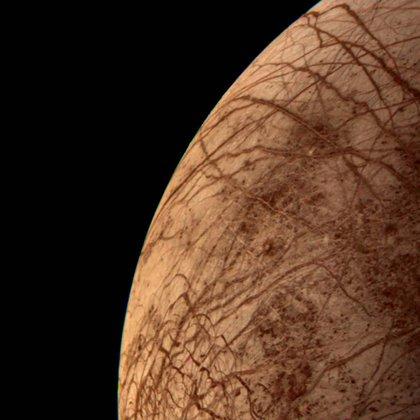 """La intriga sobre Europa. El 9 de julio de 1979, la misión Voyager 2 tomó esta imagen de la luna de Júpiter """"Europa"""". Se observaron grietas de color rojizo en su superficie helada. Se empezó a sospechar de que ese satélite natural puede contener condiciones propicias para la vida. El equipo del argentino Lucas Paganini encontró agua en forma de vapor. El vapor irrumpe en grandes géiseres en Europa. (NASA/Paganini)"""