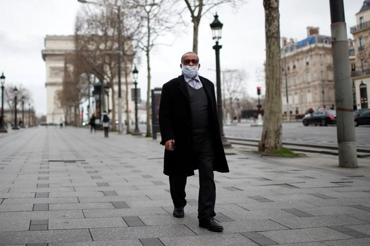 Un hombre camina por Champs Elysees, cerca del Arco de Triunfo, en una París casi desierta