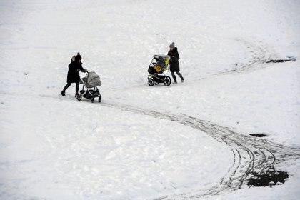 Gente paseando a sus pequeños en la nieve (Andy Buchanan / AFP)