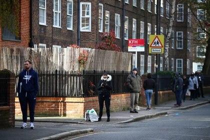 Gente siguiendo las reglas de distanciamiento social mientras hacen cola en la Oficina de Correos de Kennington, mientras continúa la propagación del coronavirus (COVID-19), Londres, Reino Unido [4 de abril de 2020] (Reuters/ Hannah McKay)