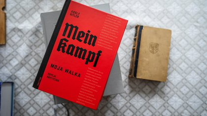 """The Polish academic edition of Adolf Hitler's 'Mein Kampf' (L) is seen next to an original edition of the book from 1942 (R) on the table of Eugeniusz Cezary Kr�l, author of the translation and historical commentary of the academic edition, in his flat in Warsaw, on January 15, 2021. - An academic edition of Adolf Hitler's """"Mein Kampf"""" is being published in Poland this week for the first time, with its editor responding to critics by calling it """"a homage to the victims"""". Hitler's inflammatory tract has been rarely published even after rights to the book, first published in 1925, became public domain in 2016. (Photo by Wojtek RADWANSKI / AFP)"""