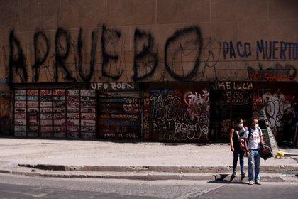 """Transeúntes son vistos bajo una pintada con la palabra """"apruebo"""", en referencia al plebiscito constitucional en Santiago de Chile (Chile). EFE/Alberto Valdes/Archivo"""