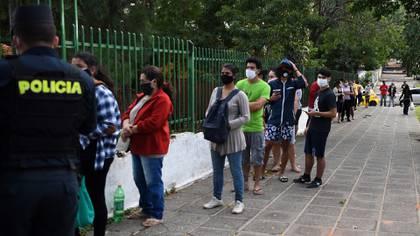 Residentes de un barrio pobre hacen fila para recibir víveres distribuidos por soldados.