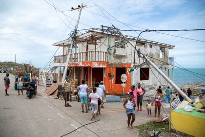 People walk near a damaged house and fallen electricity poles after the passing of Storm Iota, in Providencia, Colombia November 17, 2020. Picture taken November 17, 2020. Efrain Herrera / Colombia Presidency / Handout via REUTERS ATTENTION EDITORS - THIS IMAGE HAS BEEN SUPPLIED BY A THIRD PARTY.  DO NOT RESALS.  NO FILES.