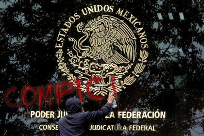 Un manifestante pinta graffiti en la fachada del Consejo de la Judicatura Federal, durante una protesta antes del sexto aniversario de la desaparición de 43 estudiantes de la Escuela Normal Rural de Ayotzinapa, en la Ciudad de México, México 24 de septiembre de 2020.