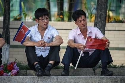 Dos ciudadanos norcoreanos sostienen banderas de ambos países en el centro de Pyongyang (AFP)