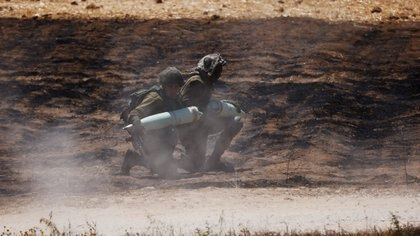 Israeli soldiers carry artillery shells in a field next to their artillery unit near the border between Israel and the Gaza Strip, on its Israeli side