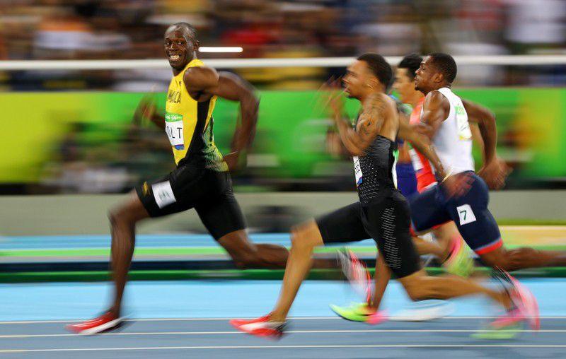Usain Bolt, de Jamaica, mira a Andre De Grasse, de Canadá, mientras compiten durante las semifinales de 100 metros masculino en los Juegos Olímpicos de Río 2016, el 14 de agosto de 2016. REUTERS/Kai Pfaffenbach
