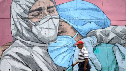 A man walks past a coronavirus-related mural, in Acapulco, Guerrero state, Mexico, on May 1, 2020. (Photo by FRANCISCO ROBLES / AFP)