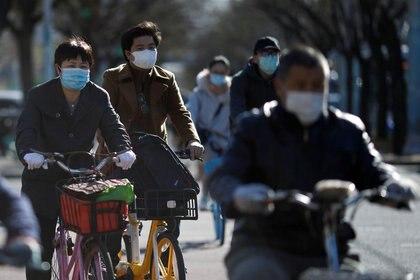 Varias personas montan bicicletas portando mascarillas para protegerse de coronavirus en Pekín. Marzo, 2020. REUTERS/Carlos Garcia Rawlins