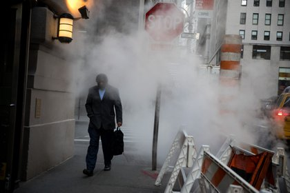 A pedestrian passes in front of a tube releasing a cloud of steam near the New York Stock Exchange (NYSE) in New York, U.S., on Monday, Jan. 7, 2019. U.S. stocks climbed following last week's rally with investors piling into small-capitalization stocks amid the resumption of trade talks with China. Photographer: Michael Nagle/Bloomberg