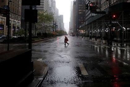 Una mujer camina bajo fuertes lluvias y vientos a través de una avenida casi vacía en Manhattan durante el brote de la enfermedad del coronavirus (COVID-19) en la ciudad de Nueva York, Nueva York, EEUU, el 13 de abril, 2020. REUTERS/Mike Segar