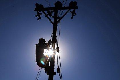 Un empleado trabaja en un poste eléctrico. EFE/ Sanjay Baid/Archivo