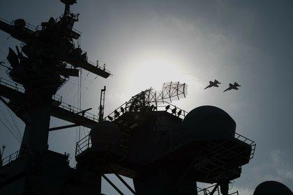 La torre del USS Lincoln, y dos F/A-18 Supr Hornet sobrevolando(AP Photo/Jon Gambrell)