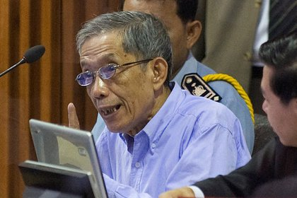 FILE PHOTO: Khmer Rouge commander Kaing Guek Eav, also known as Duch, speaks to his attorneys moments before the start of his trial on the outskirts of Phnom Penh February 17, 2009. REUTERS/Adrees Latif/File Photo