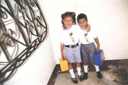 Paola y William de niños antes de su primer día de clases.