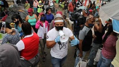 FOTO DE ARCHIVO-Walter Rivera, director del mercado mayorista Coche, anuncia con un megáfono las reglas para evitar el coronavirus (COVID-19) a locatarios y clientes en Caracas, Venezuela. 23 julio 2020. REUTERS/Manaure Quintero