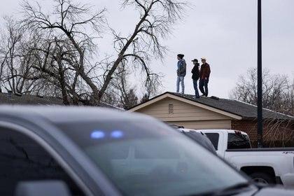 La gente se para en un techo en el perímetro del lugar de la masacre del supermercado de King Soopers en Boulder, Colorado (Reuters)