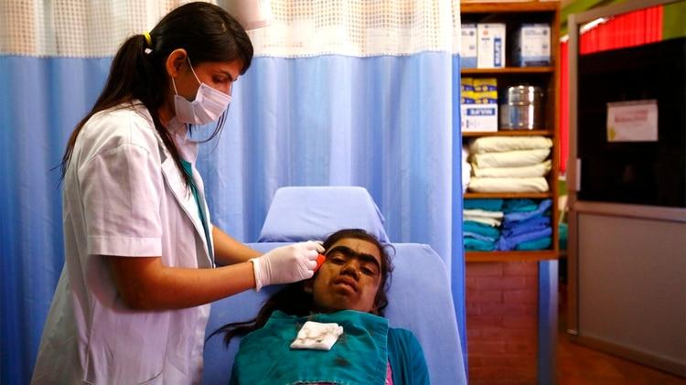 """Manjura Budhathoki, de 14 años, se afeita el pelo antes del tratamiento de depilación láser en el Hospital Dhulikhel de Kavre, en las afueras de Katmandú, el 22 de octubre de 2013. Sufre el """"síndrome del hombre lobo"""" y se está sometiendo a depilación láser para disminuir sus síntomas. (Reuters)"""