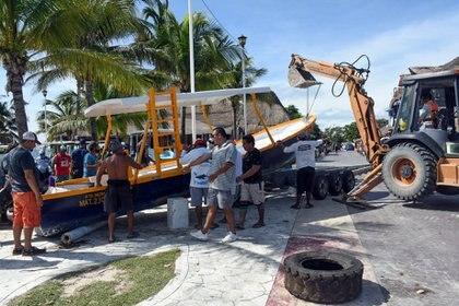 Trabajadores y pescadores del área costera de Puerto Morelos protegen sus embarcaciones (Foto: Elizabeth Ruiz/ AFP)