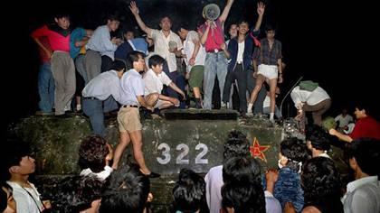 Manifestantes pro democracia sobre un vehículo blindado del Ejército Popular de Liberación