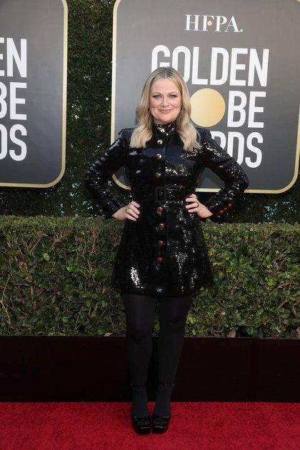 Amy Poehler, una de las presentadoras de la noche, lució un traje de paillettes negro de mangas largas abotonado con medias traslúcidas y zapatos de taco cuadrado cerrados