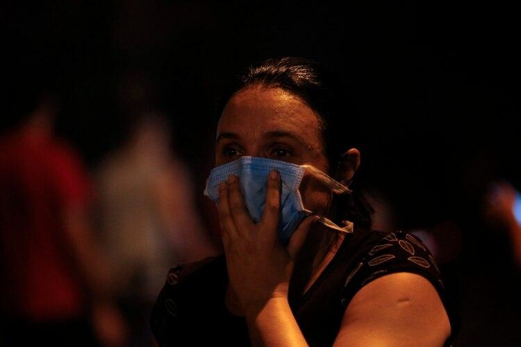 Una mujer mira atentamente el incendio (MAURO PIMENTEL / AFP)