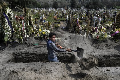A gravedigger works at the San Miguel Xico cemetery in Valle de Chalco, Mexico state, Mexico, on September 24, 2020, amid the COVID-19 coronavirus pandemic. (Photo by PEDRO PARDO / AFP)
