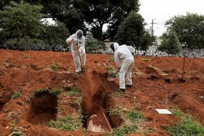 Sepultureros con trajes protectores entierran el ataúd de una persona que murió de la enfermedad por coronavirus (COVID-19), en el cementerio de Vila Formosa, el más grande de Brasil, en San Pablo [13 de mayo de 2020] (Reuters/ Amanda Perobelli)