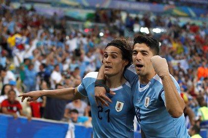 En la imagen, los jugadores uruguayos Edinson Cavani y Luis Suárez festejando un gol de Uruguay. Foto: EFE/Antonio Lacerda