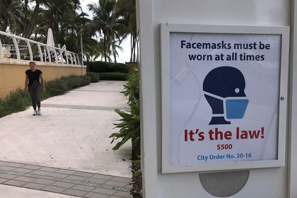 A person walks past a sign warning to wear a mask, on July 6, 2020, in Florida, United States.  EFE / Ana Mengotti / Archive