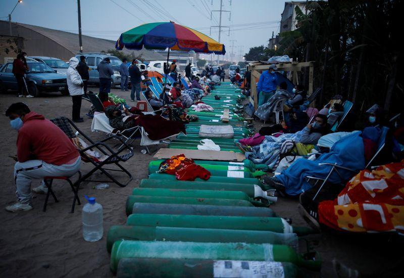 Gente espera junto a tanques de oxígeno vacíos para llenarlos para los pacientes que sufren de COVID-19 en Lima, Perú, el 25 de febrero de 2021 (REUTERS/Sebastián Castañeda)