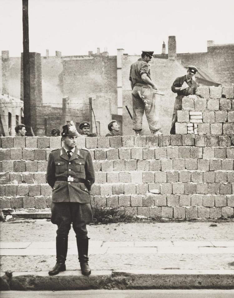 Un policía de Berlín Oeste se para frente al muro de hormigón que divide Berlín Este y Oeste. A lo largo de la calle Bernauer, los obreros de Berlín Este añaden bloques para aumentar la altura de la barrera el 11 de octubre de 1961 (Foto de Everett/Shutterstock (10293355a))