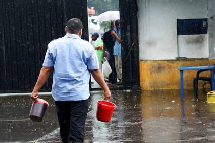 Un trabajador le lleva sangre en envases a personas que esperan a las afueras de un matadero en San Cristóbal, Venezuela